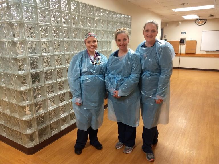 PHOTO, courtesy of McLaren Northern Michigan: Melissa Perry, RN, BSN, Karen Gardener, RN, Stacey Forbes, RN, BSN, ONC, wearing the Petoskey Plastics-made isolation gown.