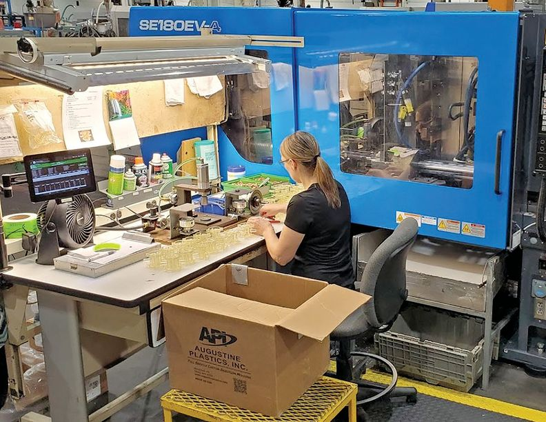 An operator at Augustine Plastics Inc. assembles a valve unit for an oxygen concentrator.